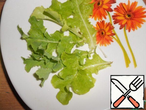 Wash the lettuce leaves, dry them and put them on a platter.