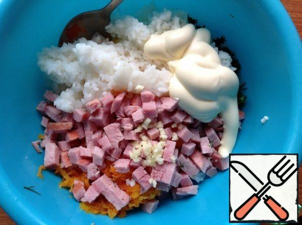 Wash the rice in cold water and allow the excess liquid to drain. Add the rice to the salad , pass the garlic through the press. Cut the ham into small cubes , add sour cream or mayonnaise. Gently mix.