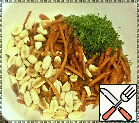 After the time has passed, remove the carrots from the refrigerator and put them in a container. Fry the peanuts for 2 minutes in the microwave and peel them. Finely chop the greens. Add the peanuts, herbs, and vegetable oil to the carrots and mix thoroughly.
