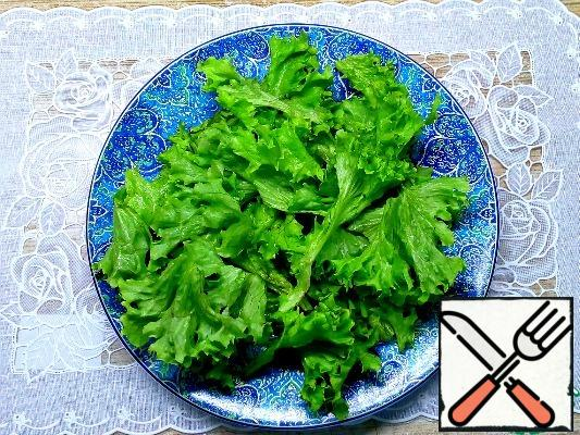 Wash the lettuce leaves, shake off the water, and tear them with your hands on a plate.