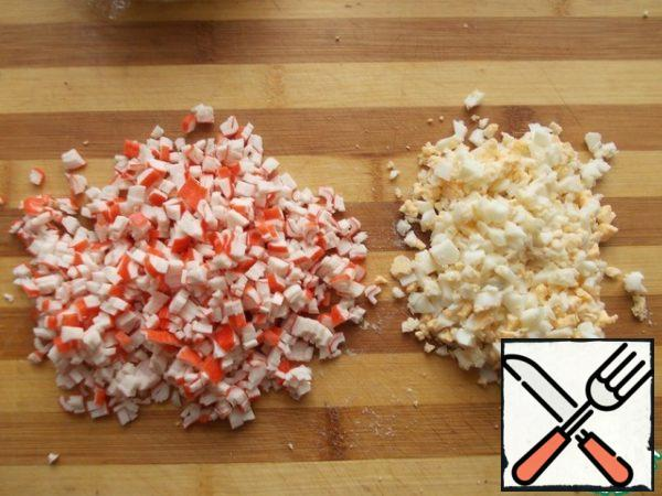 Cut the egg and crab sticks finely.