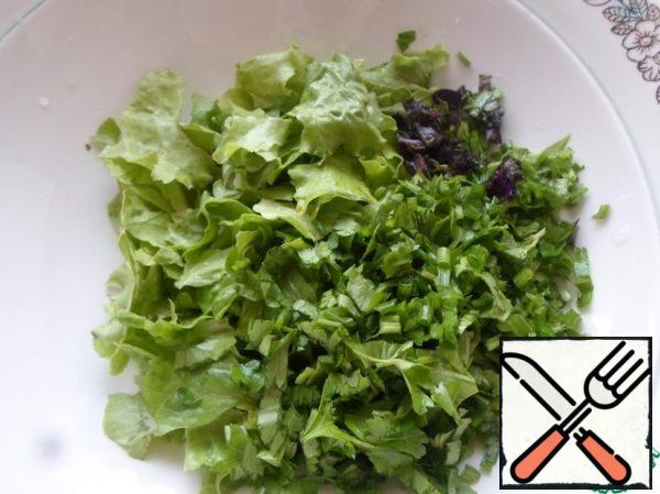 Wash the lettuce leaves and tear them into small pieces. Chop the greens with a knife.
