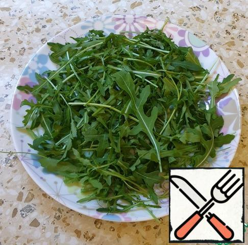 Cook the eggs for 4 minutes in boiling water and remove the shell. Put the washed arugula on a plate.