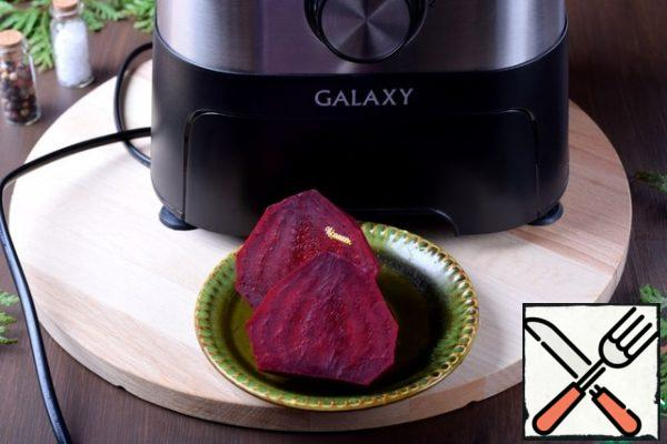 While the meat is cooking, let's make a side dish of beetroot. Peel the beets. I cut it in half to make it easy to load it into the combine.
