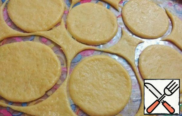 Roll out the dough into a thin layer. Cut circles with a glass, in diameter , so that they are larger than cupcake molds.