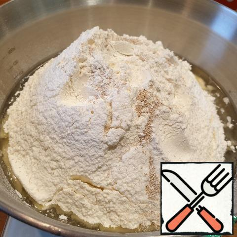 While the filling cools , knead the dough. Strain the pickle from the pickled tomatoes, heat a little until warm, add salt, sugar, and vegetable oil. Mix and add the sifted flour and yeast.