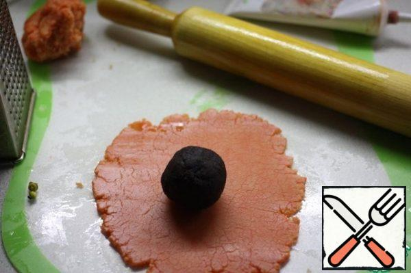Add dye to the marzipan. Roll out 2 mm thick. Wrap each balloon. Remove the excess.