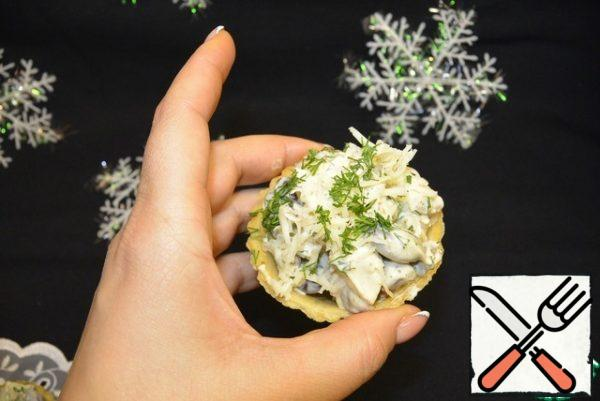 Fill the tartlets with salad. Garnish with grated cheese, chopped dill and roasted pine nuts.