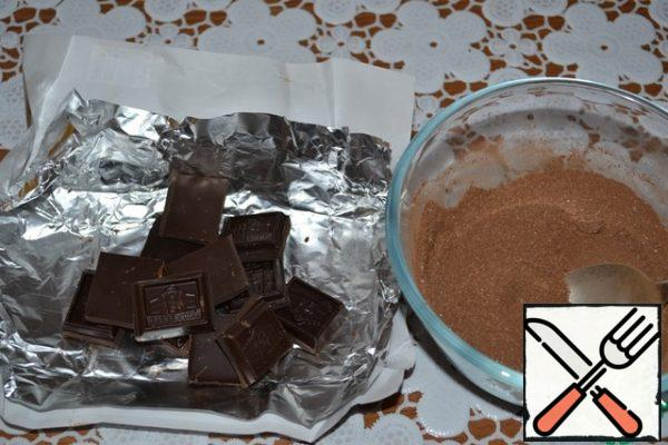 Preparing a velvet truffle biscuit: break the dark chocolate. Mix sugar with cocoa.