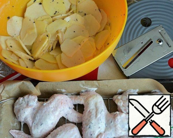 Put the wings on the grill, add salt to the potato slices, put them in the marinade from the wings, and mix.
