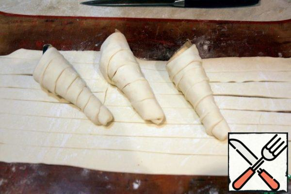 Defrost the dough, roll it out a little, cut it into narrow strips, and screw it into cones ( I have homemade ones) Bake until Golden and cool.