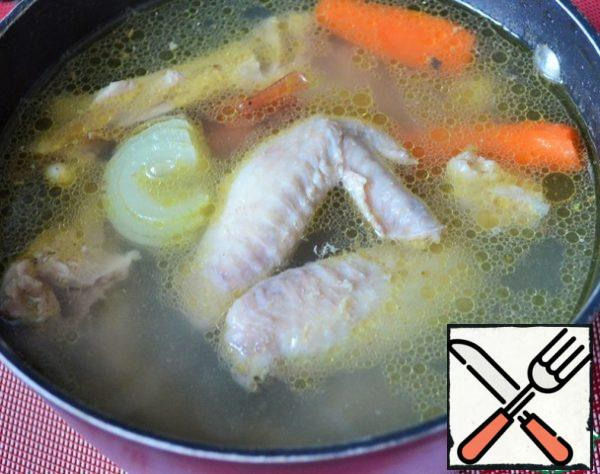 Put the wings and chicken bones in cold water, add a small onion and carrot. Cook until tender and season with salt.