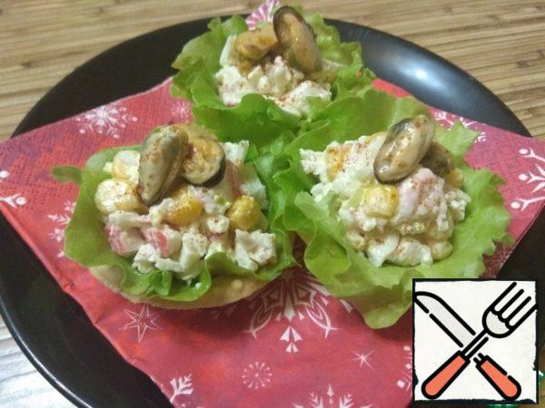 Ready salad spread out on tartlets, put mussels on top. Garnish with a pinch of sweet paprika and lettuce leaves.