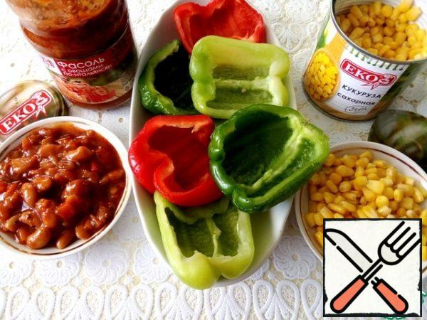 Cut the bell pepper in half, remove the seeds, and wash. Open a jar of sweet corn and beans with vegetables in Italian.