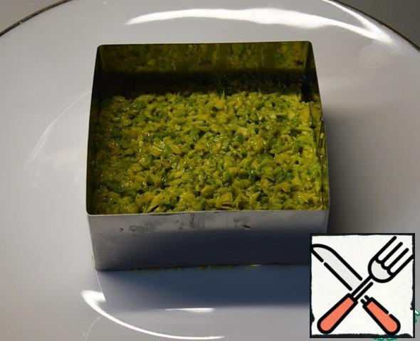 Fill the square form to form a salad with a layer of avocado, seal.