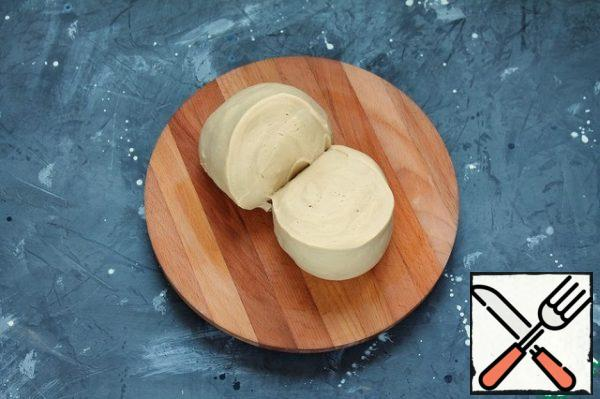Gradually add the remaining flour and knead a smooth, elastic, non-sticky dough to the hands and surface. If necessary, you can add up to 30 g of flour and knead again. Put the dough in a bowl, cover with cling film and leave for 10 minutes. Mix for another 1 minute and leave for 30 minutes.