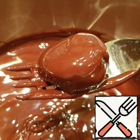 Meanwhile, melt the remaining chocolate in a water bath. Remove from the refrigerator and use a fork to roll the billet on all sides in chocolate, then put it on parchment for a couple of minutes, so that the chocolate cools down a little.