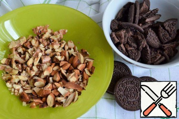 Before assembling the cake, prepare everything for the filling. Peel the nuts, fry them in a dry pan, and remove the husks if possible. Chop the cookies and nuts. Leave some for decoration.