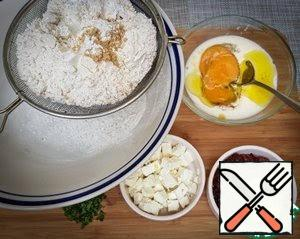 Cut feta cheese and tomatoes into small cubes. Sift all the flour, salt, baking powder, pepper, and mustard powder into a large bowl. Pour the bran from the sieve into a bowl. Beat the egg, milk, and tomato oil lightly.