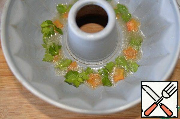 Take the form in which you will prepare aspic. For a presentable presentation, I took a form with a ring in the middle. At the bottom, put the carrots, parsley leaves on top and pour a little broth with gelatin, so that in the future the carrots look beautiful on top. Put it in the refrigerator for 10 minutes to freeze.