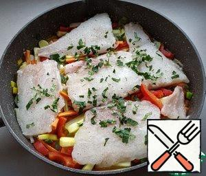 As soon as the vegetables boil, stir and put the fish on top. Sprinkle with parsley, leaving the parsley to decorate the finished dish.