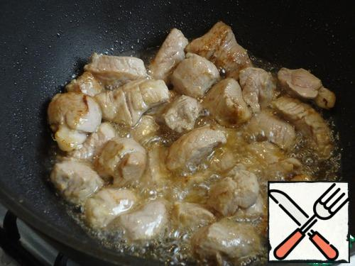 Pour the oil into the cauldron, heat it as much as possible. Throw the meat, everything should boil, splash and sizzle loudly.