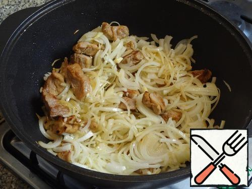 As soon as the meat is browned-throw the onion and mix, the cauldron is slightly cold from the meat, so the fire is not reduced.