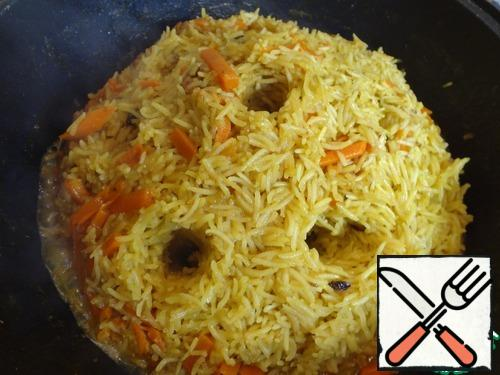 I don't cover it with a lid, just flatten the rice and wait until it absorbs all the water. As soon as there is no water left on the surface, we form a hill of rice in the center of the cauldron, and make holes so that the remaining water evaporates faster around the edges and inside.