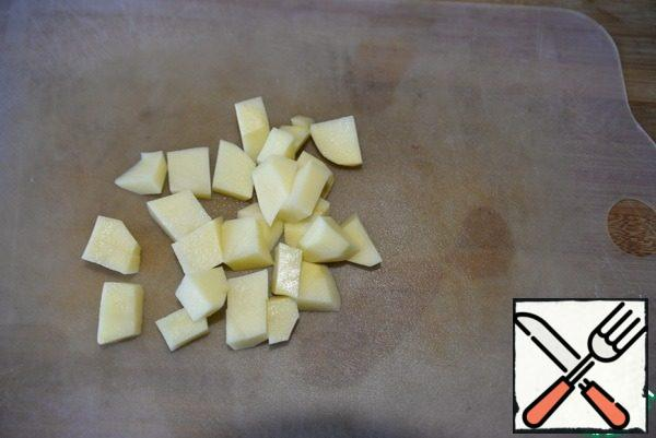 Peel the potatoes, cut them into cubes, and put them in the soup. Bring to a boil and cook over medium heat for 10 minutes.