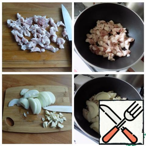 For this dish, I will take pork with lard. This is so that no oil is used in the dish. Cut the pork into small pieces and put it in a saucepan. Put it on the fire and let the fat melt a little. Put garlic finely chopped and onion, cut into half rings, to the meat. Just a little fried.