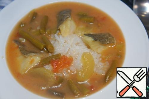 Spread the boiled rice on plates, pour the soup and serve.