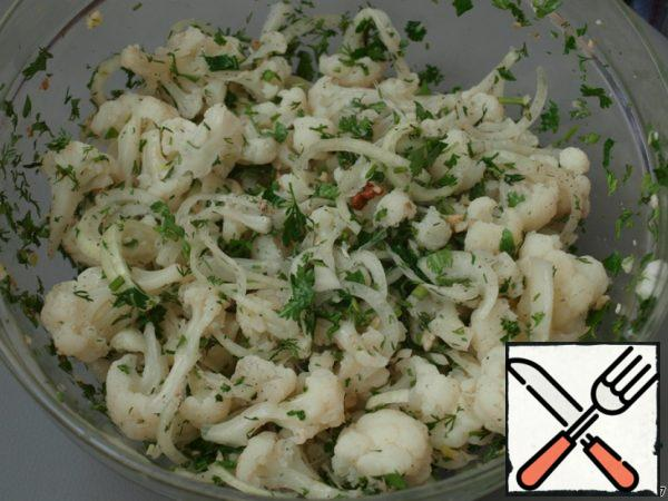 Cool the cabbage, disassemble it into stumps or cut it into small pieces. Cut the onion into half rings and chop the greens. Mix, add the crushed walnuts and squeeze out the garlic.