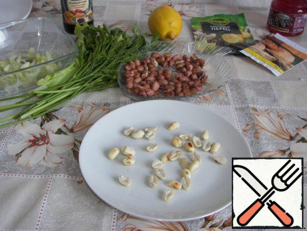 Fry the peanuts in a dry pan for 5 minutes, until the husk begins to easily remove. Do not overcook. Peel the nuts and divide them into halves.
