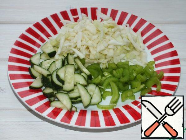 Meanwhile, you need to cut cucumbers, cabbage and celery.