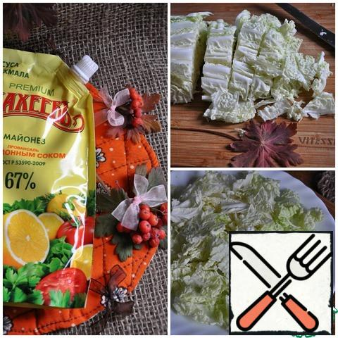 First of all, cut the Peking cabbage into large pieces. Cabbage will play the role of a pillow for the rest of the ingredients. Arrange the cabbage on a wide plate.