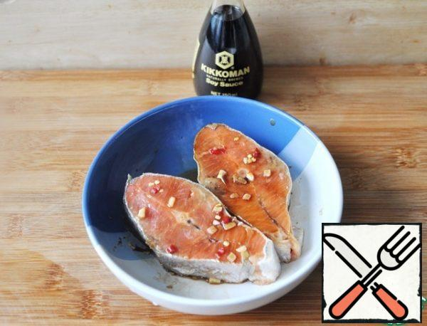 Dip the salmon steaks in the marinade and put them to marinate in a cold place for 20 minutes.