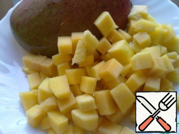 Peel the mango and separate the flesh from the bone in slices, cut into cubes.