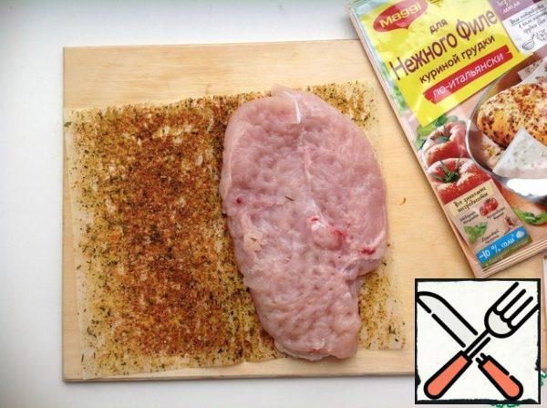 Wash the chicken breast, dry it and beat it with a hammer to a thickness of 1.5 cm. Expand the frying sheet, place the chicken fillet on one half, cover with the second half of the sheet. Press down with your palm.
