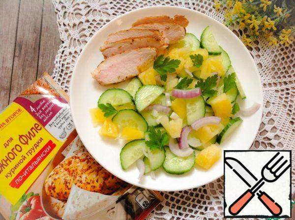 Add the red onion, cucumber and pineapple slices to the bowl, add the dressing, and mix. Put the salad and chicken slices on a serving dish and sprinkle with herbs.