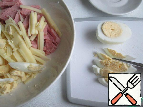 Cut the ham into cubes. Semi-hard cheese first cut into plates and then each plate-thin strips. Cut the eggs in half lengthwise and then in strips.