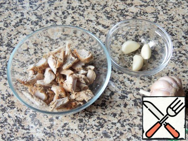 Cut the meat into small pieces. This can be baked or boiled chicken, the remains of a barbecue. Chop the garlic.