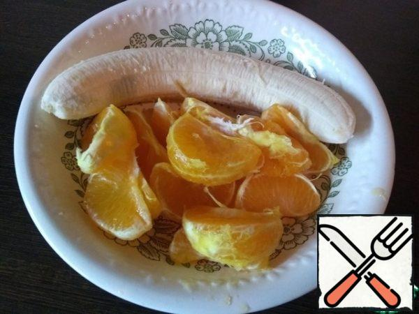 Peel the banana and tangerines. If You like a more uniform consistency of the drink, then you should remove the film from the tangerines as much as possible. Take them apart into slices. If the tangerines are simply separated into slices, without clearing the films, the drink is obtained with the pulp, like juice)