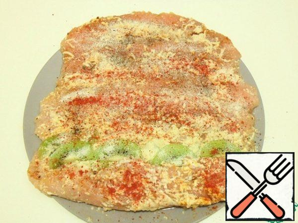On the edge of the flattened fillet, put kiwi slices, sprinkled with spices and powdered gelatin.