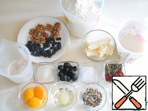 This is the abundance you will need to prepare holiday bread. All products should be warm, and the butter is soft, the consistency of sour cream, heat it a little. In 50 ml of warm milk, dilute the yeast and a pinch of sugar, cover with a napkin and remove to a warm place, so that they gain strength - activated. Sift the flour. Separate the yolks from the whites and mix well, without whipping. Nuts, seeds and raisins are sorted, so that you do not get anything extra.