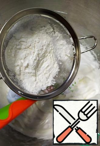 As soon as the meringue is ready, sift the cornstarch and spatula by hand gently and stir well.