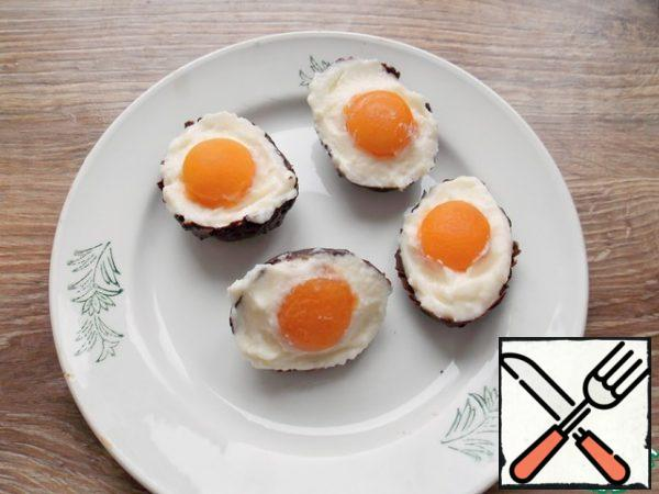 Fill the chocolate shells with a creamy mass and immediately drown the yolk of the apricot. Put in the freezer for 10-15 minutes, then transfer to the refrigerator. It is advisable to fill them no more than 3-4 hours before serving.