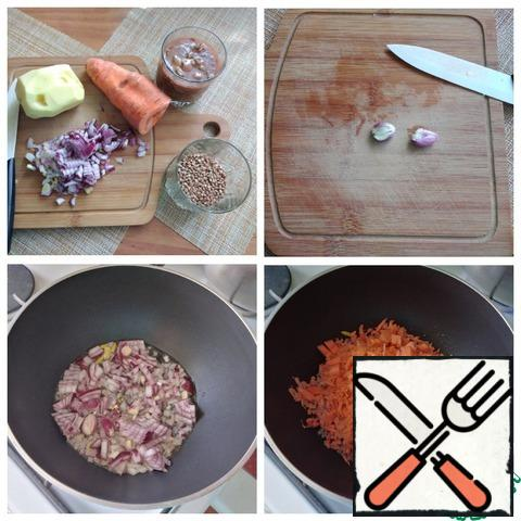 We prepare everything that we need for soup. I always chop sprat in tomato with a fork. My garlic is young and I crushed the cloves right in the skin with the flat side of a knife. I use red onions, you can take onions. Finely cut it. Carrots 2/3 of the grated medium, and 1/3 of the cut into a small cube. We will need a pot with a thick bottom, where I will first simmer the vegetables, and then cook the soup. If you don't have one, use a regular pan and pan with high walls. Put the pan on the fire, poured olive oil (you can replace it with sunflower oil), warmed it and put the crushed garlic. After a minute, you can remove it, it will give its flavor to the oil. Spread the onion. Slightly fried it until soft and put the carrots. Stir, reduce the heat to a minimum, cover with a lid and then cook the vegetables for 5 minutes.