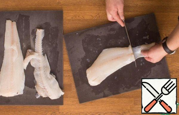 To remove the skin from the fillet, place the knife horizontally between the skin and the meat on the tail of the fillet halves and hold the skin horizontally with one hand. You still have the skin and a piece of the purest fillet. Repeat the operation with the second part.