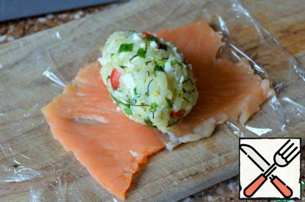 """Put the salmon plates on the food film, roll them lightly through the film with a rolling pin or mash them with a fork. Place the """" egg """" in the middle."""