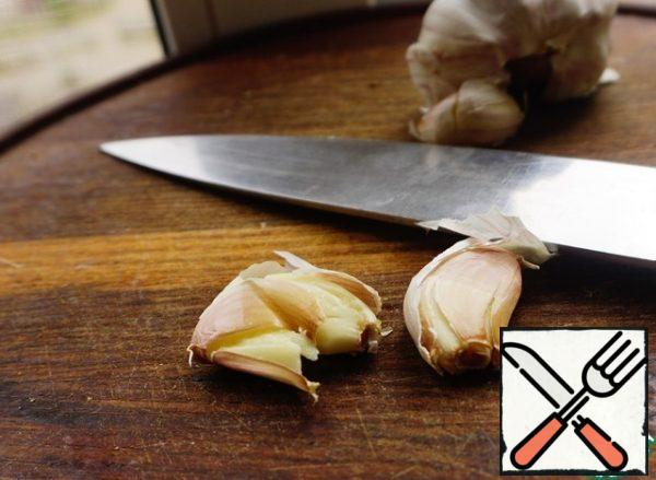 Two cloves of garlic are pressed down with a knife. Don't clean it.
